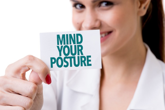 "Young lady holding a ""mind your posture"" sign note"