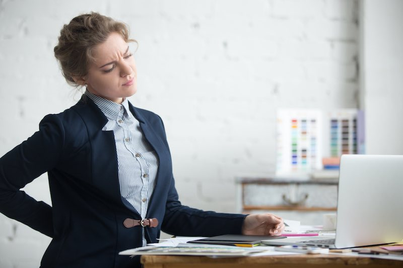 Woman feeling pains at the desk