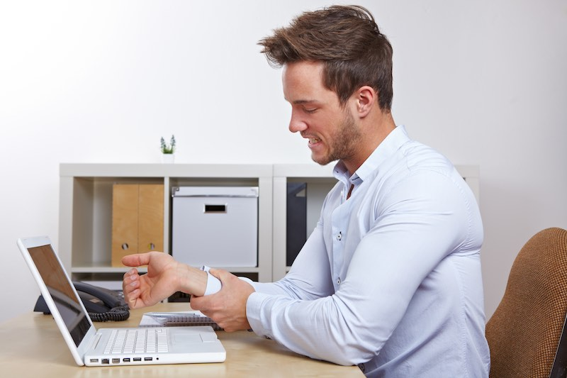 Man feeling wrist pain while typing on a laptop
