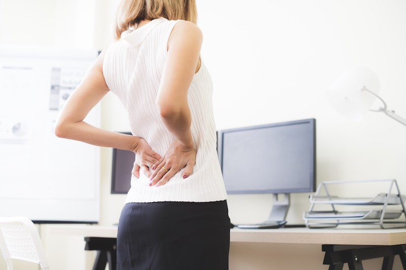 Woman standing by her desk holding her hip