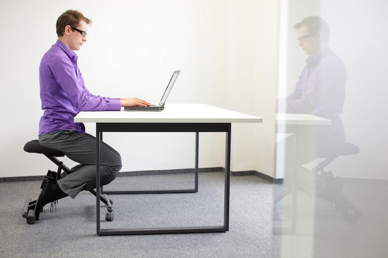 Man using saddle chair while working in office