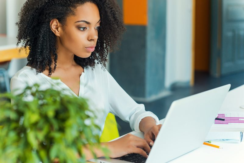 African-American lady working on a white laptop concentrating on her tasks