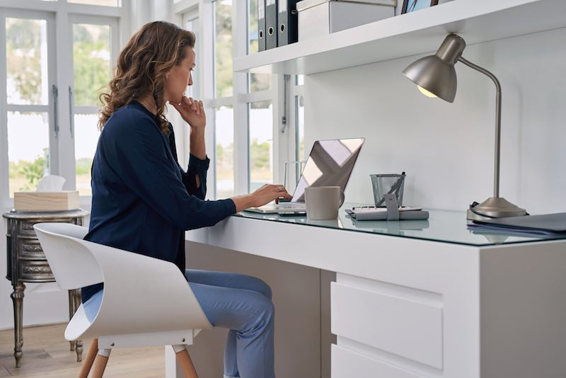 Blonde Lady working from home at a white minimal office desk