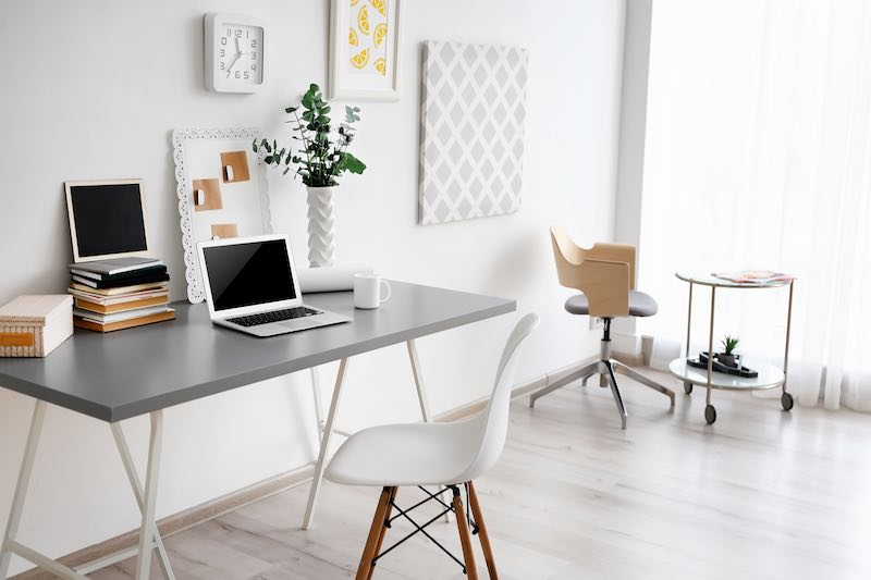 Simple minimal office with a white chair and office plants