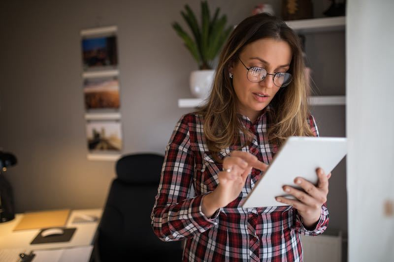 young lady wearing glasses using her tablet in her home office